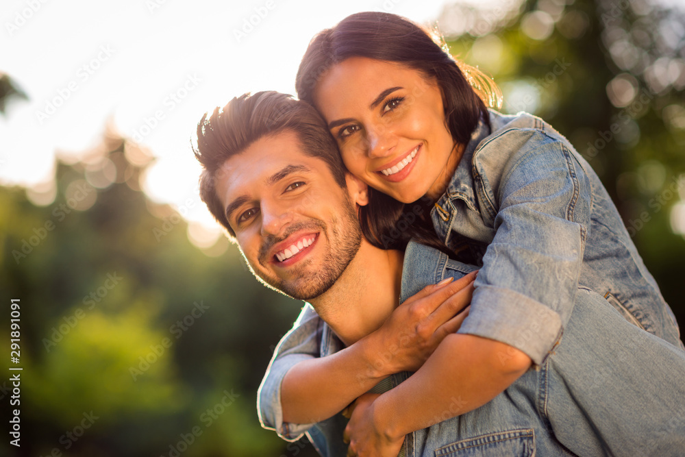 Fototapeta Close up photo of charming spouses having brunet hair cuddling piggyback outside in forest