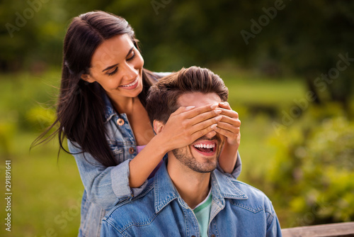 Poster Attraction parc Close up photo of charming couple hiding eyes sitting on bench wearing denim jeans outside in park