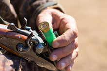 Close Up Of Hunter Loading Shotgun,  Holds A Gun And Ammunition In His Hand.
