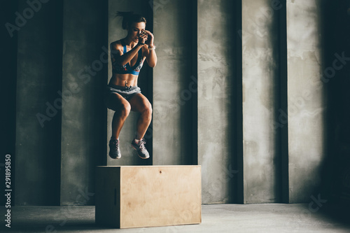Photographie  Fitness woman jumping on box while training at the gym,girl doing cross fit exercise