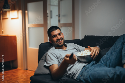 man relaxing on sofa eating popcorn and watching television. evening scene - 291897472