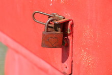Red Rusty Padlock On A Red Ste...