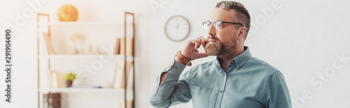 Photographie  panoramic shot of handsome businessman in shirt and glasses talking on smartphon