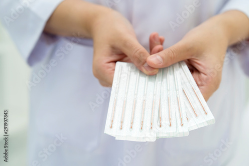 Photo doctor or Acupuncturist showing kit needles for acupuncture in hand