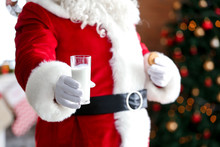 Santa Claus With Milk And Cookie In Room Decorated For Christmas, Closeup
