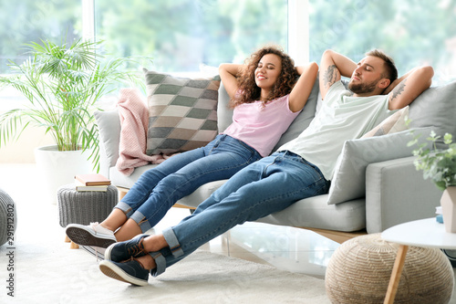 Happy young couple relaxing on sofa at home Fototapet