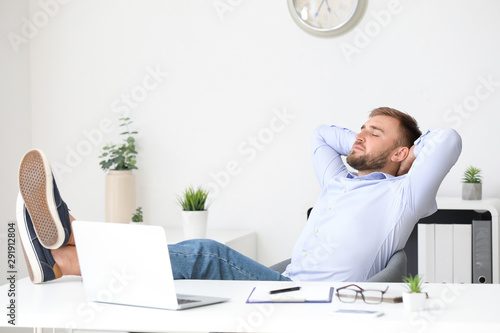 Photo Handsome young man relaxing at workplace