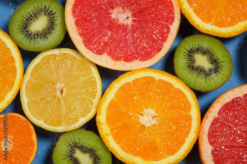 Fotografie, Obraz  Assortment of various cut raw fruits on blue background, full frame