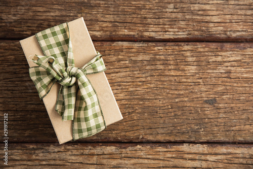Gift box with ribbon on wooden table