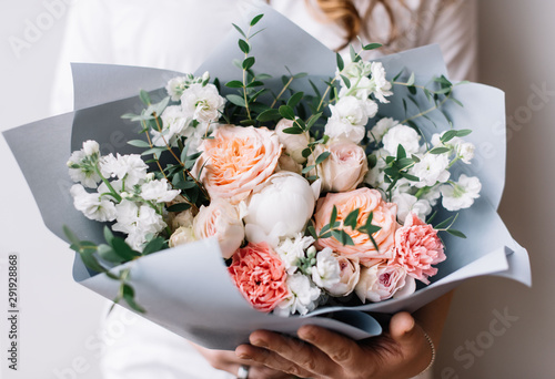 Foto Very nice young woman holding a beautiful blossoming flower bouquet of fresh mat