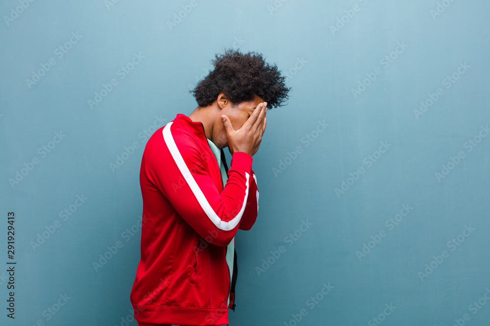 Fototapeta young black sports man covering eyes with hands with a sad, frustrated look of despair, crying, side view against grunge wall