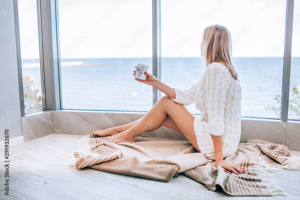Fototapeta Young happy woman in a white knitted dress enjoying sea view next to big window with cup of tea. Panoramic window. Floor covering