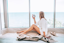 Young Happy Woman In A White Knitted Dress Enjoying Sea View Next To Big Window With Cup Of Tea. Panoramic Window. Floor Covering