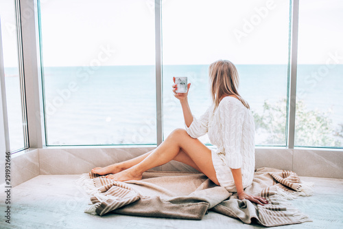Obraz Young happy woman in a white knitted dress enjoying sea view next to big window with cup of tea. Panoramic window. Floor covering - fototapety do salonu