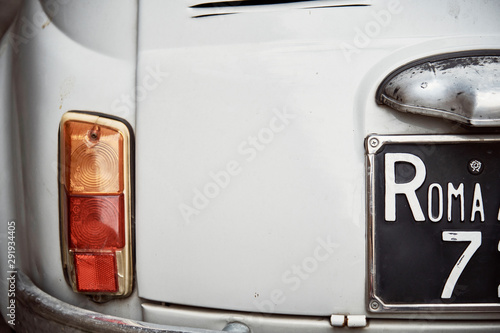 Detail view of an old Fiat 500 car typical of Italy in grey color parked Wallpaper Mural