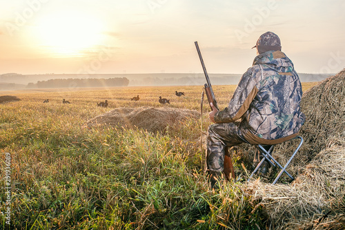 Hunter in camouflage with a gun hunting on black grouse. Wallpaper Mural