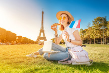 Happy Asian Girl With French Flag Eating Croissant And Learning Foreign Languages On Laptop With Eiffel Tower In The Background. The Concept Of Modern Distance Learning For Students In Paris
