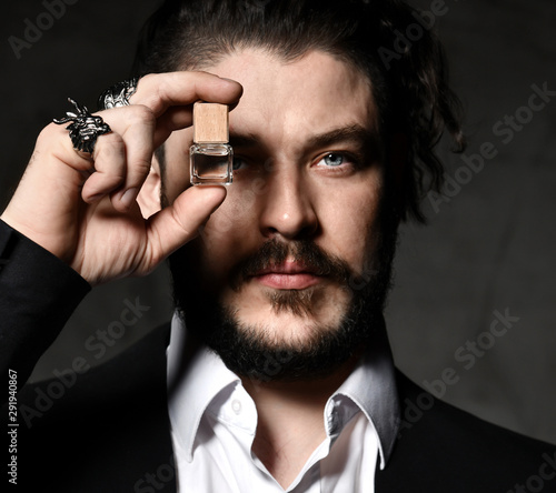 Valokuva Brutal man with beard and modern hairstyle wearing business classic suit shows s