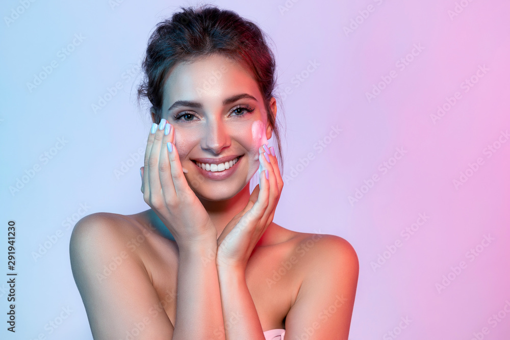 Fototapety, obrazy: Portrait of beautiful woman applying skin cleansing foam and looking at camera with joyfulness. Wonderful young model using facial moisturizing cosmetic. Beauty and clean skin concept