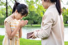 Asian Mother Hands Open Wallet...