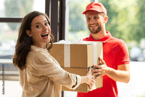Vászonkép selective focus of happy woman receiving carton boxes from cheerful delivery man