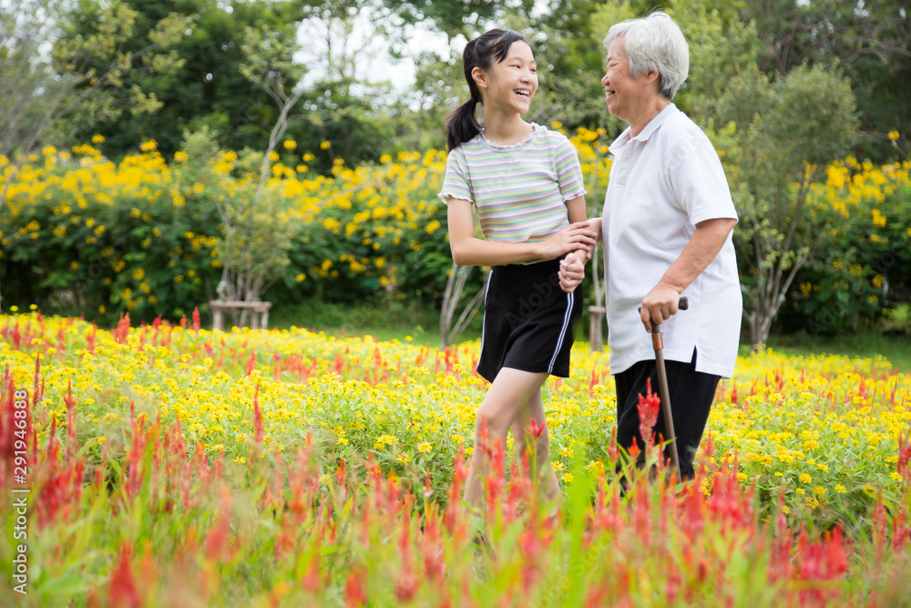 Fototapety, obrazy: Happy asian senior grandmother and granddaughter walking in blooming garden,simple stress reduction,enjoying nature,smiling child girl holding hand of elderly woman care,support,health care concept