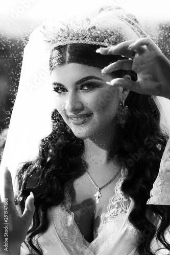 Portrait of an incredibly beautiful girl in robe and wedding make-up, beautiful eyes, painted lips and a sincere smile and a view to the window waiting for the wedding. Black and white