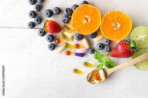 Fototapeta Multivitamins and supplements with fresh and healthy fruits on white wooden background. obraz