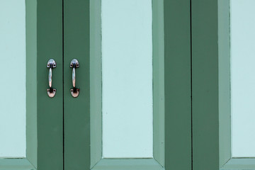metal handle of a green classic wooden window.