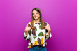 Leinwanddruck Bild - young pretty woman looking proud, positive and casual pointing to chest with both hands against purple background