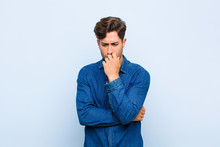 Young Handsome Man Feeling Serious, Thoughtful And Concerned, Staring Sideways With Hand Pressed Against Chin Against Blue Background