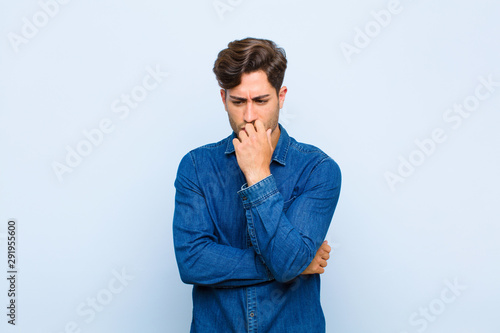 Fotografía young handsome man feeling serious, thoughtful and concerned, staring sideways w