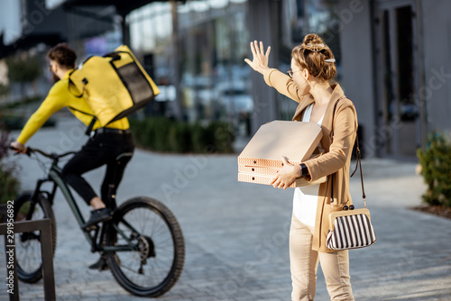 Misguided woman calling back a courier that ride away on the background, deliver Billede på lærred