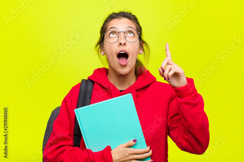 Fototapeta  young pretty student looking shocked, amazed and open mouthed, pointing upwards