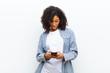 Leinwandbild Motiv young pretty black woman with a smart phone against white wall