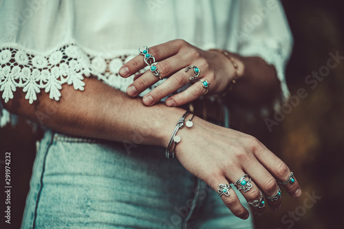 Foto auf Gartenposter Boho-Stil Fashionable boho chic woman in a white short blouse with silver turquoise jewelry. Boho fashion. Stylish girl wearing silver rings with turquoise stone in hippie style.