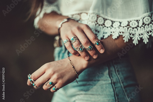Fotobehang Boho Stijl Fashionable boho chic woman in a white short blouse with silver turquoise jewelry. Boho fashion. Stylish girl wearing silver rings with turquoise stone in hippie style.