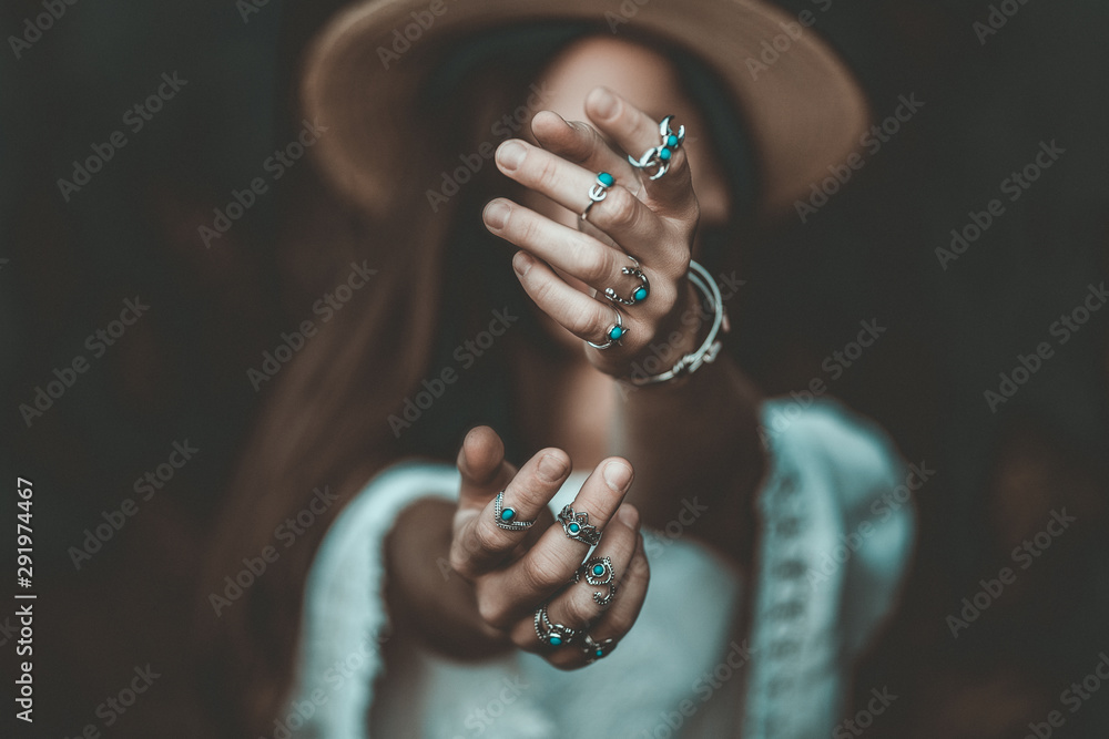 Fototapeta Boho chic woman in a straw hat in a white short blouse and with silver turquoise jewelry. Boho fashion. Hippie style, stylish girl with silver rings