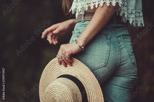 Fotobehang Boho Stijl Stylish fashion woman in jeans shorts and in a white short blouse with silver turquoise rings holds a straw hat. Denim style