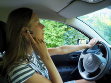 Young Girl Behind The Wheel Of A Car Burns Through The Device Hands Free