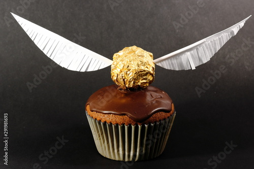 One muffin with Golden Snitch decoration on black background. Harry Potter theme.