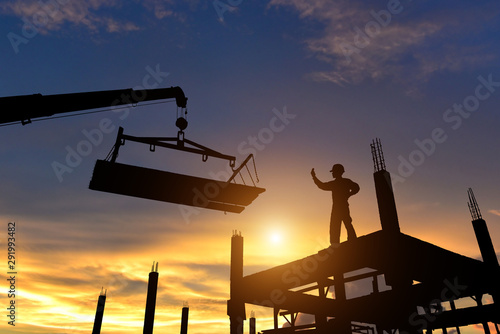 Obraz Workers in safety equipment installed concrete panels in the construction site at sunset. - fototapety do salonu