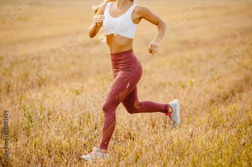 Young woman blonde runner in sportswear runs on field offroad park Billede på lærred