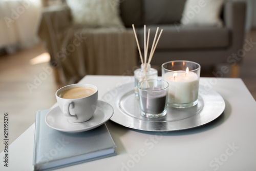 Obraz hygge and aromatherapy concept - coffee, candles, book and aroma reed diffuser on table at home - fototapety do salonu
