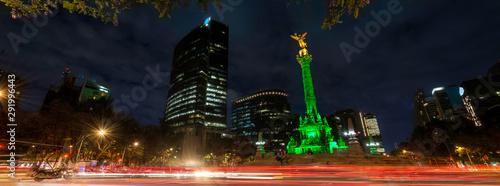 Obraz Panoramica de larga exposicion en el  Angel de la Independencia de la Ciudad de Mexico, de noche y con edificios de fondo. - fototapety do salonu