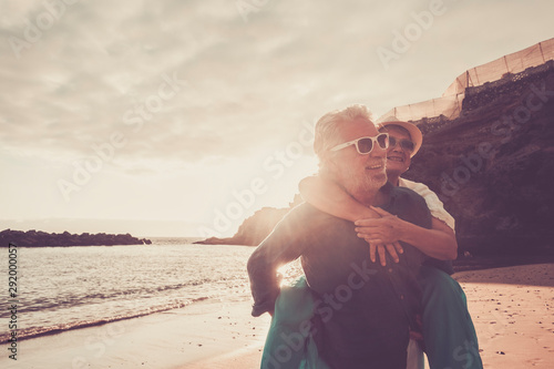 Obraz beautiful couple of seniors at the beach having fun together and playing - mature man carry his wife woman with love and forever life concept - sea or ocean in the background -   retired lifestyle - fototapety do salonu