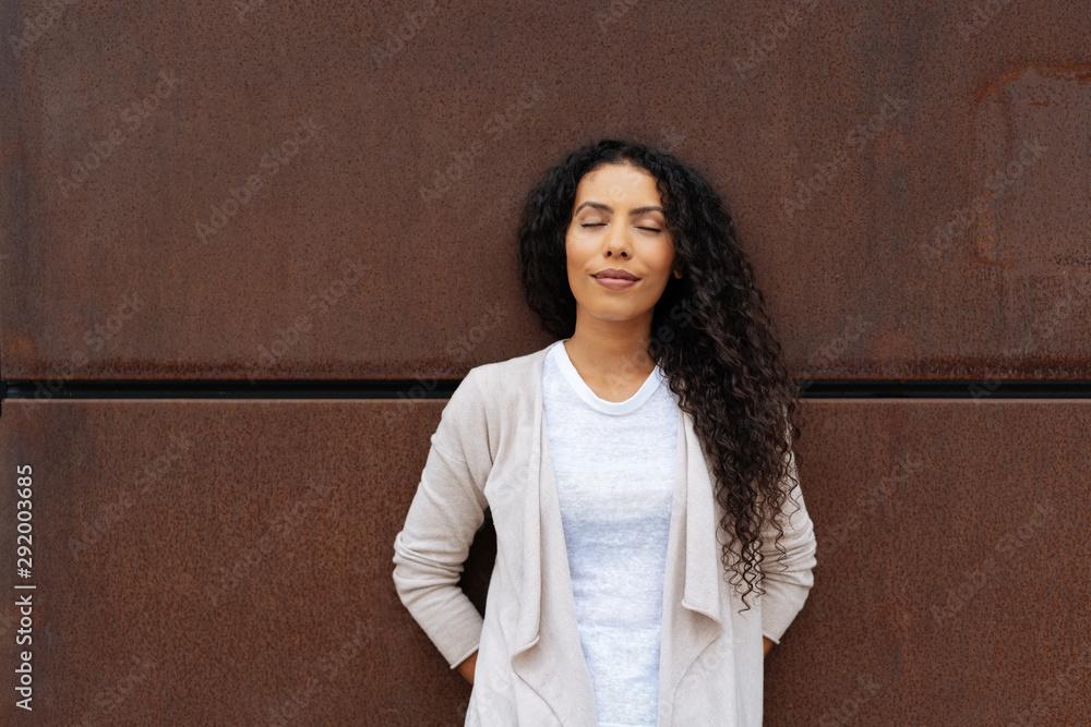 Fototapeta Woman standing relaxing against a brown wall