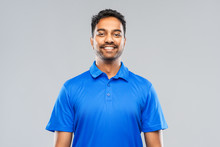 Emotion, Expression And People Concept - Smiling Indian Man In Blue Polo Shirt Over Gray Background