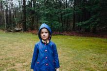 Young Girl In Blue Raincoat Looking Pensively At The Camera.