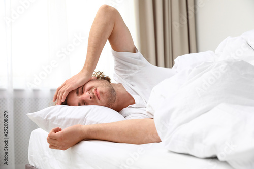 Fotomural Sleepy young man lying on pillow at home. Bedtime